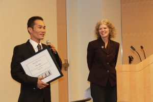 Photo of Sue Burrell presenting award to Tung Nguyen